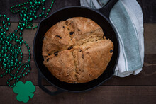 Photograph Of Irish Soda Bread Baked In A Cast Iron Skillet With Shamrock Beads For Saint Patrick's Day
