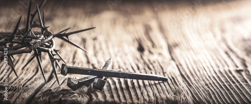Fotografia Three Crucifixion Spikes Wooden Table With Crown Of Thorns And Vintage Effect -