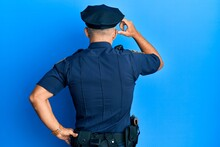 Middle Age Handsome Man Wearing Police Uniform Backwards Thinking About Doubt With Hand On Head