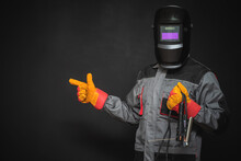 Welder Man In The Helmet With A Welding Terminals Is Showing By The Index Finger On The Copy Space On The Black Background.