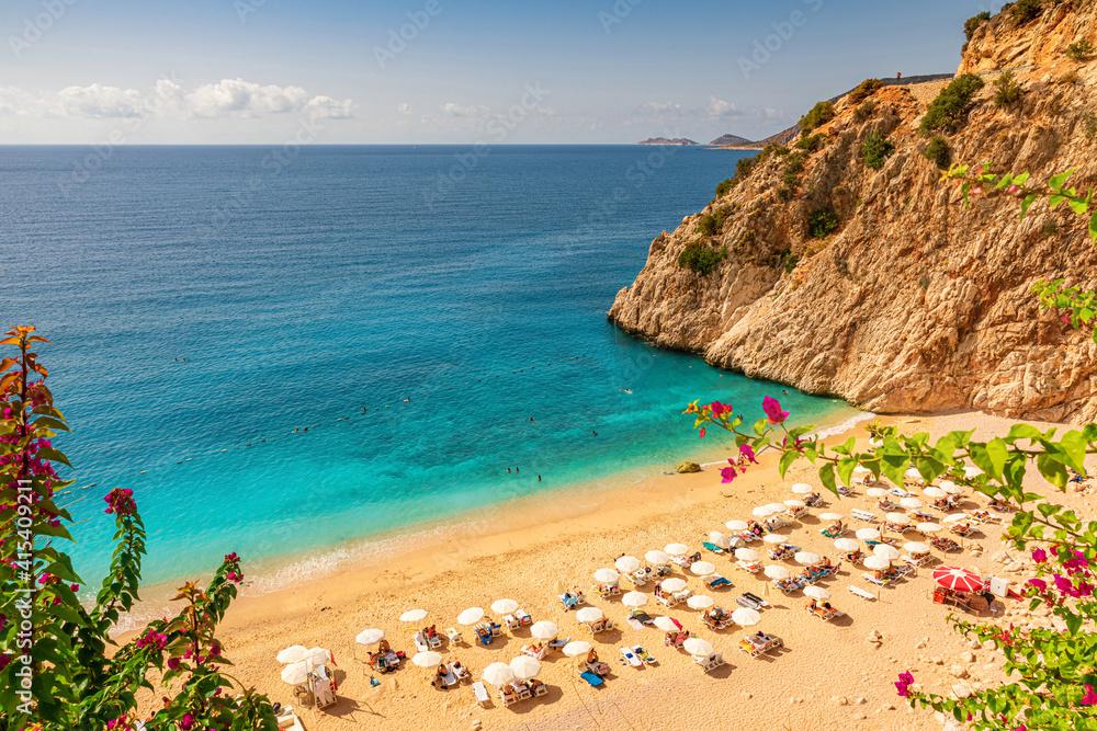 Fototapeta Kaputas beach with blue water on the coast of Antalya region in Turkey with sun umbrellas on the beach