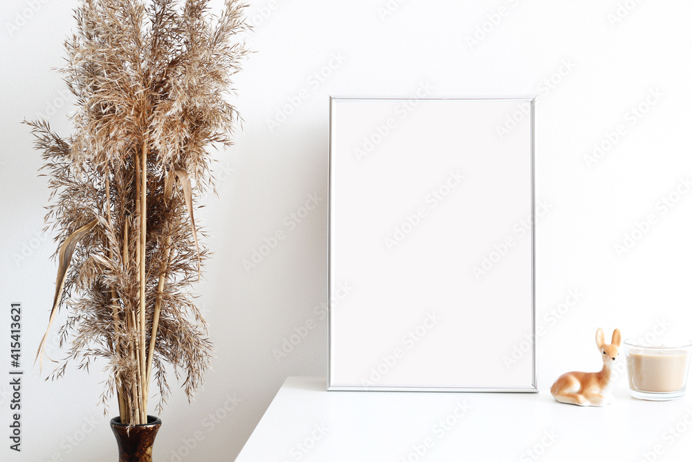 Fototapeta picture frame mockup in white simple interior with dry grass and candle