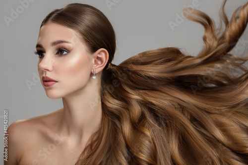 Beautiful fashionable young woman with long wavy and shiny hair. Brunette with curly hairstyle hair flying up