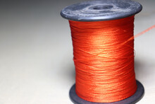 Closeup Of Vibrant Orange Yarn Reel On A White Cloth