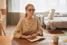 Warm Toned Portrait Of Modern Blind Woman Reading Braille Book While Sitting At Table In Cozy Home Interior With Guide Dog In Background, Copy Space