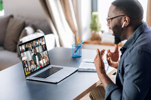 Business Brainstorm, Online Video Meeting, Virtual Conference With Multiracial Colleagues. African American Man Communicate With Business Partners By Video Call Uses Laptop And App, Work From Home