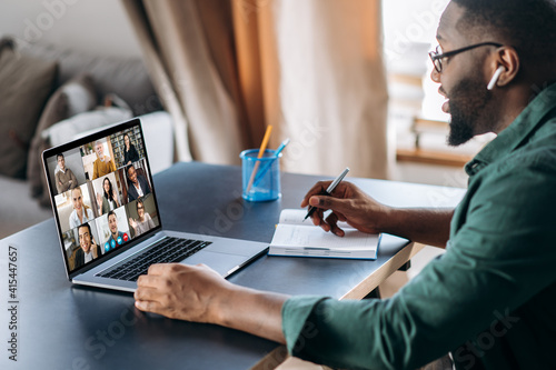 Obraz Online business briefing. Male African American employee speak on video call with diverse multiracial colleagues, on laptop screen diverse business people, meeting online, group brainstorm - fototapety do salonu