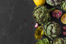 Cooking Concept. Fresh Raw Artichokes Vegetable With Lemon, Garlic, Olive Oil And Pepper On Black Background. Top View