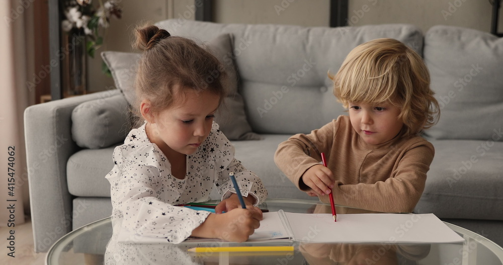 Fototapeta Happy cute little boy and girl drawing with colored pencils in paper album, sitting together at table in living room. Adorable small children siblings involved in creative domestic activity.