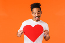 Cheerful African-american Hipster Guy With Afro Haircut, Moustache, Boyfriend Want Surprise Girlfriend Valentines Day, Holding Heart Card, Looking Lower Left Corner And Smiling, Orange Background