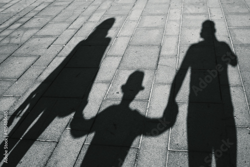 Fotografie, Tablou Shadow on pavement of a family: mom with dad and son walking together, holding hands