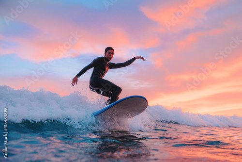 Canvas Print Young surfer boy, surfing at sunset on a Portuguese beach