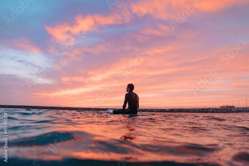 Young surfer boy, surfing at sunset on a Portuguese beach Fototapeta