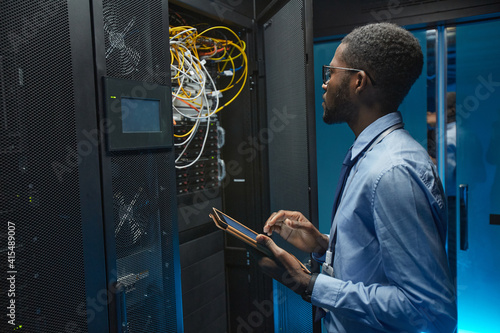 Side view portrait of African American man standing by server cabinet while work Wallpaper Mural