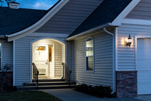 A Home's Front Porch With A Lockbox Attached To The Railing Of The Steps Is Illuminated At Evening.