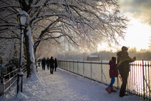 People Walking Under The Trees Covered In Snow And Watching Sunset In Central Park