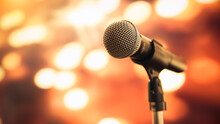 Public Speaking Backgrounds, Close-up The Microphone On Stand For Speaker Speech Presentation Stage Performance With Blur And Bokeh Light Background.
