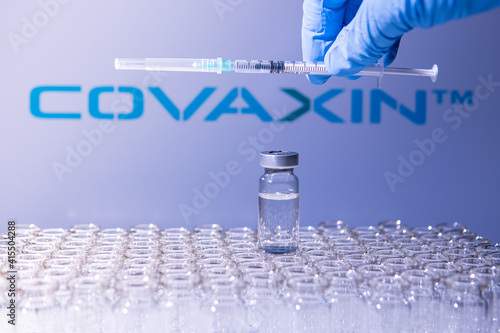 Fototapeta premium Toronto, Ontario, Canada - February 14, 2021 : A health worker prepares to administer a shot of the Indian vaccine Covaxin. Name of company is blurry and vials containing Covid 19 vaccine.