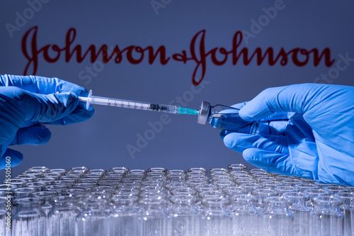 Fototapeta premium Toronto, Ontario, Canada - February 14, 2021 : A health worker prepares to administer a shot of the American vaccine Johnson and Johnson. Name is blurry and vials containing mRNA technology vaccine.