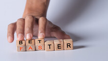 """Hand Holding Dice With Text For Illustration Of """"better And Faster"""" Words"""