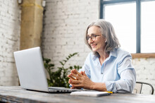 Senior Businesswoman Sitting At The Desk, Looking At Webcam And Talking With Client Online Or Watching Tutorial, Elder Female Office Worker Or Therapist Having Appointment, Virtual Meeting Via Laptop