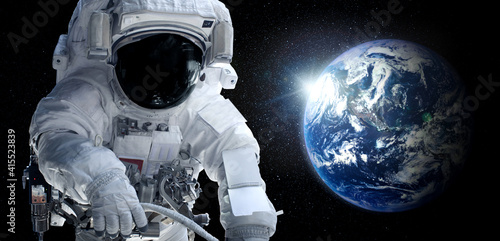 Astronaut spaceman do spacewalk while working for space station in outer space Fototapeta