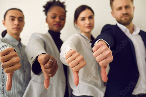 Fototapeta Group of young diverse people giving thumbs down, hands in closeup