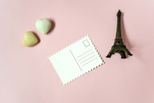 Blank Postcard And Decorative Elements (two Stone Hearts And A Souvenir Eiffel Tower) On Pink Background, Empty Postcards, Postcrossing, Mockup. Top View, Flat Lay. Selective Focus. Copy Space.