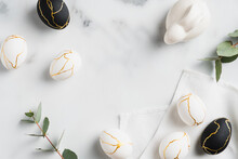 Easter Flat Lay Composition. Easter Bunny, Luxury White And Black Easter Eggs Decorated Gold And Eucalyptus Leaves On Marble Table. Flat Lay, Top View