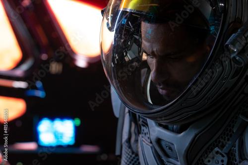Fotografie, Obraz Portrait of African American Black male astronaut inside spaceship cockpit