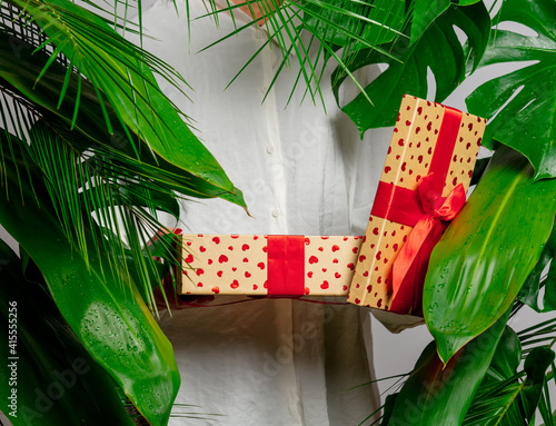 female hand holding gift box on background with palm leaves © Masson