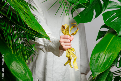 Woman in white shirt show measure tape near palm leaves. © Masson