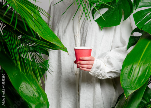 female hand holding paper cup on background with palm leaves © Masson