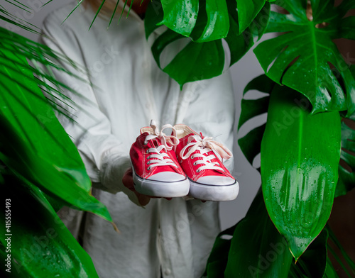 Woman in white shirt show red gumshoes near palm leaves. © Masson