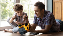 Close Up Caring Father And Little Son Fixing Toy Car, Lying On Warm Wooden Floor At Home, Smiling Young Dad And Cute Adorable Boy Using Screwdriver, Having Fun, Spending Leisure Time Together