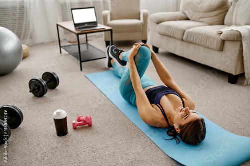 Fototapeta Smiling girl sits on floor, online fit training obraz