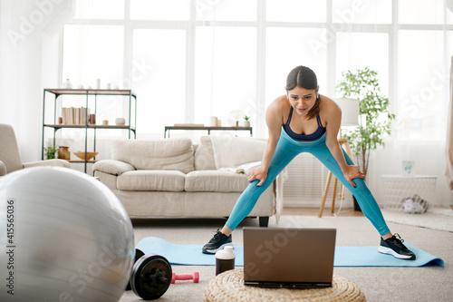 Fototapeta Girl standing at laptop, online fitness training obraz