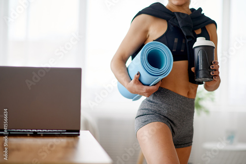 Fototapeta Woman holds mat, online fitness training obraz