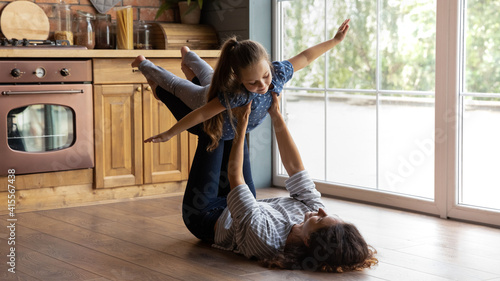 Fototapeta Caring mother holding little daughter pretending flying with hands outstretched, lying on warm wooden floor in kitchen, loving young mum carrying adorable girl, family engaged in funny activity obraz