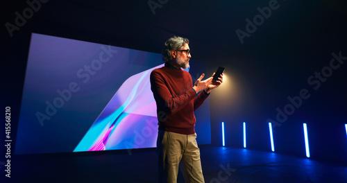 Middle aged speaker explaining smartphone features Fototapet