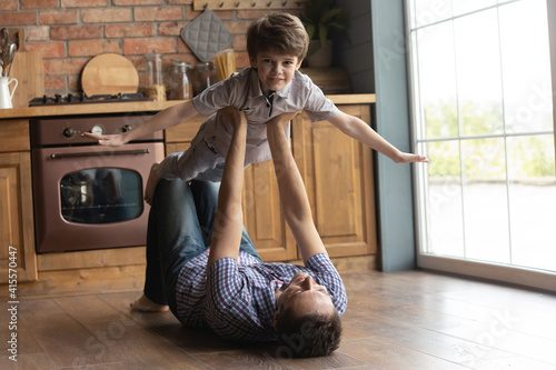Fototapeta Portrait little boy pretending flying, playing fanny game with father, caring loving young dad holding lifting son, lying on warm wooden floor in kitchen, family spending leisure time at home obraz