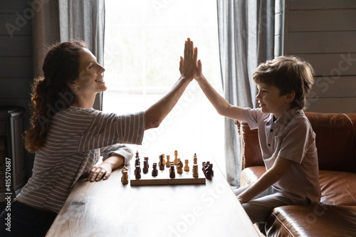 Fototapeta Side view smiling mother and little son playing chess, teacher and student giving high five, celebrating win, successful game result, family involved in board game activity, having fun at home obraz