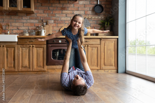 Fototapeta Portrait caring father holding little daughter pretending flying with hands outstretched, lying on warm wooden floor in kitchen, loving dad carrying adorable girl, family engaged in funny activity obraz