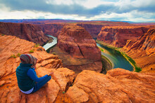 Person Meditating In Front Of A Scenic Horseshoe Bend, Page, Arizona, USA