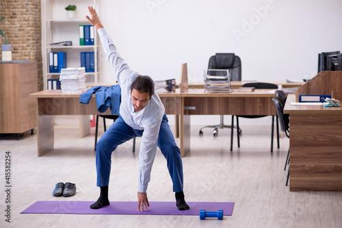 Fototapeta Young male employee doing sport exercises during break obraz