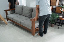 A Gray Sofa Carried By Two Men In The Living Room. Moving Concept
