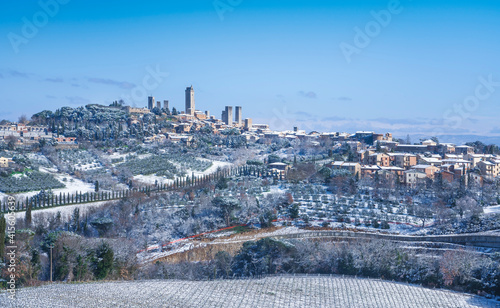 Fototapeta premium San Gimignano snowy town, towers skyline and vineyards. Tuscany, Italy