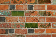 Background: Close-up Of Colorful Red Tiles On A Wall, Some Of Them Glazed With Green Glass And Some Burnt To Black Color
