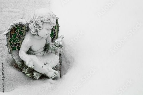 Foto cherub in snow white space for text to right