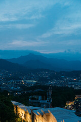 View of on top of Seoul city wall at dusk with city and mountain behind.